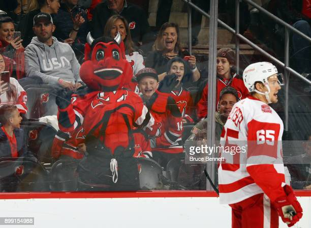 The New Jersey Devils mascot tries to get the attention of Detroit Red Wings defenseman Danny DeKeyser at the Prudential Center on December 27 2017...