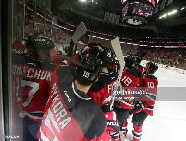 The New Jersey Devils surround Travis Zajac in celebration after Zajac scored the game-winning goal to give the Devils a 3-2 overtime win against the...