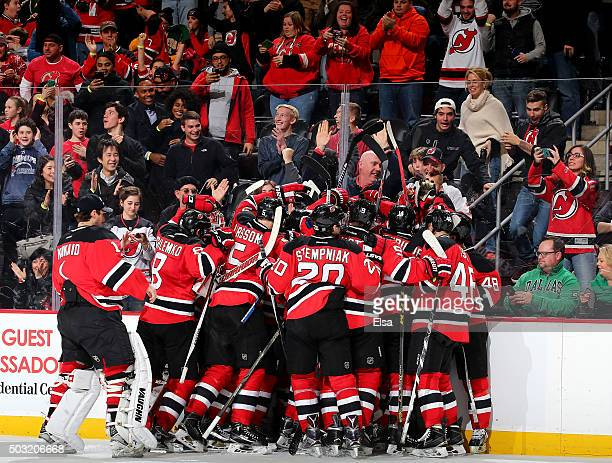 The New Jersey Devils team surrounds John Moore after he scored the game winner in overtime against the Dallas Stars on January 2,2016 at Prudential...