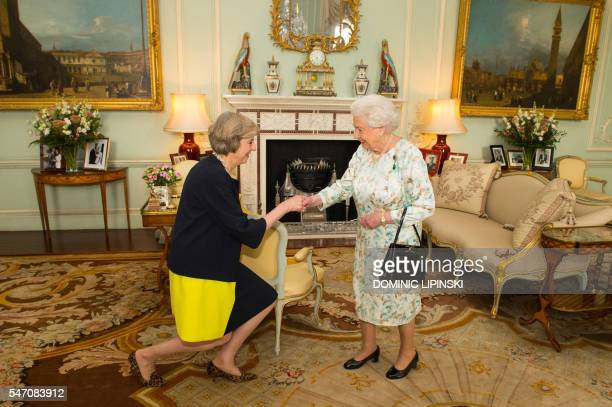 The new leader of the Conservative Party Theresa May kneels as she is greeted by Britain's Queen Elizabeth II at the start of an audience in...