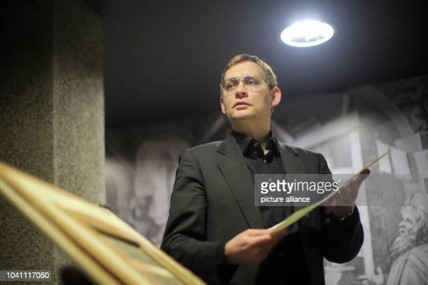 The new Mainz 2016 writer in residence writer Clemens Meyer stands with a freshly printed page by a printing press in the Gutenberg Museum during a...