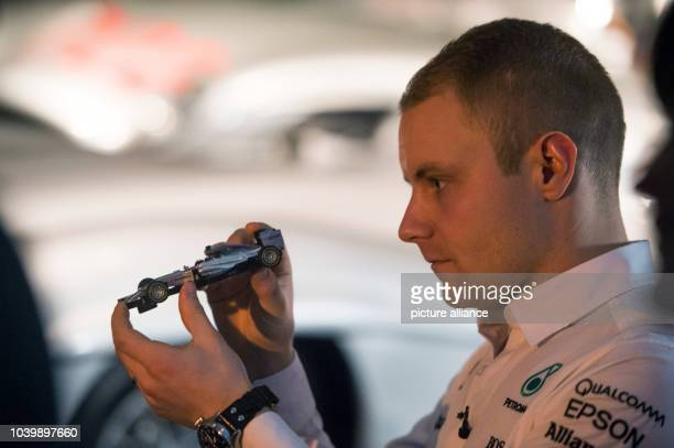 The new Mercedes driver Valtteri Bottas holds up a miniature formula one race car during a press conference at the Mercedes-Benz Museum in Stuttgart,...