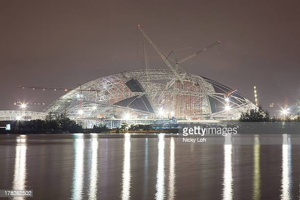 The new National Stadium inside the Sports Hub area is reflected on the Kallang River on August 28 2013 in Singapore The Ministry of Trade and...