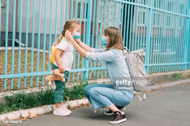 the new normal: mother and daughter wearing protective face masks walking to school together, coronavirus prevention concept - aplanar a curva imagens e fotografias de stock