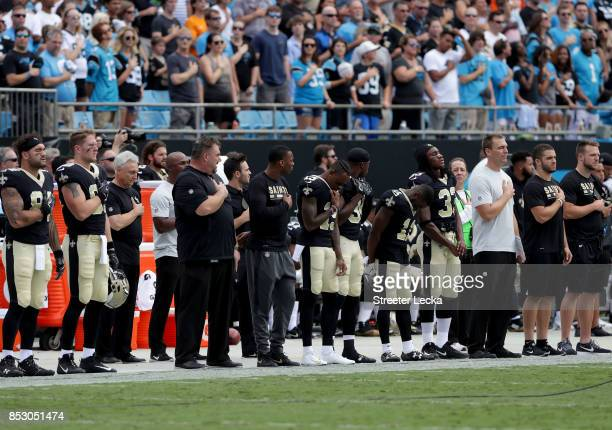 The New Orleans Saints stand during the National Anthem before their game against the Carolina Panthers at Bank of America Stadium on September 24...