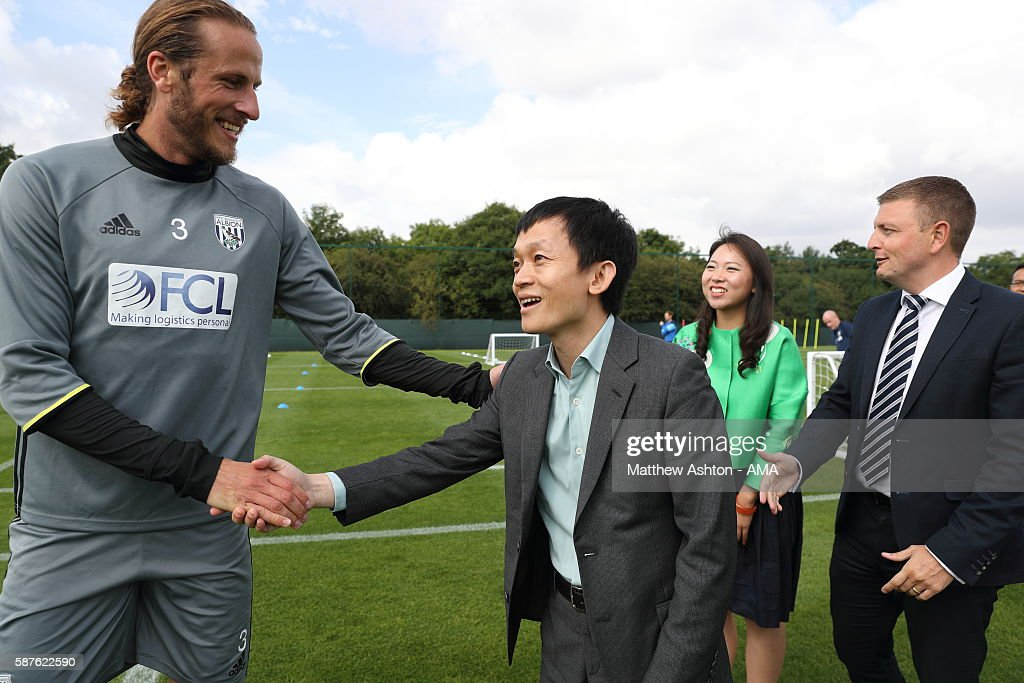 The new prospective owner of West Bromwich Albion, Guochuan Lai from Yunyi Guokai (Shanghai) Sports Development Limited meets defender Jonas Olsson whilst on a tour of the club on August 8, 2016 in West Bromwich, England.