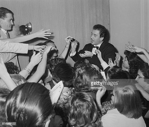 The new rage in singing Italian singer Domenico Modugno has his hands full as he hands out autographs after his debut at Carnegie Hall in New York...