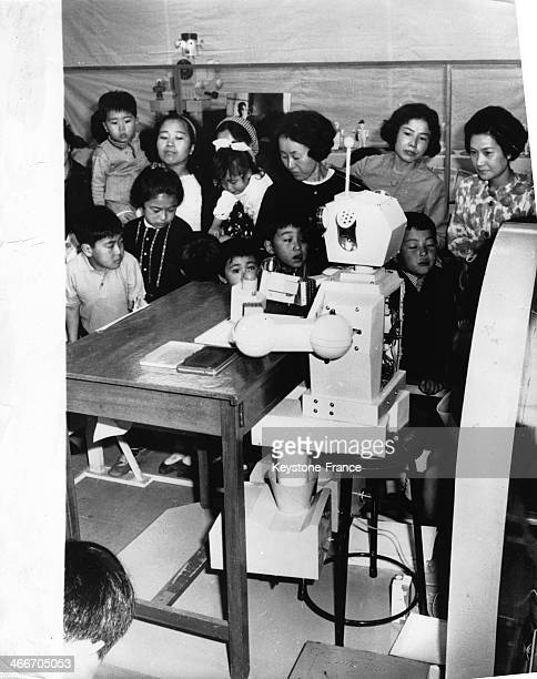 The new secretary 'Miss Robot' is shown working away at her desk she can write draw stamp letters she is delvered by Japanese robot engineer Jiro...
