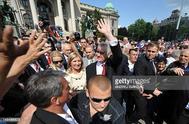 The new Serbian President Tomislav Nikolic flanked by his wife Dragica, greets his supporters in front of the National assembly building in Belgrade...