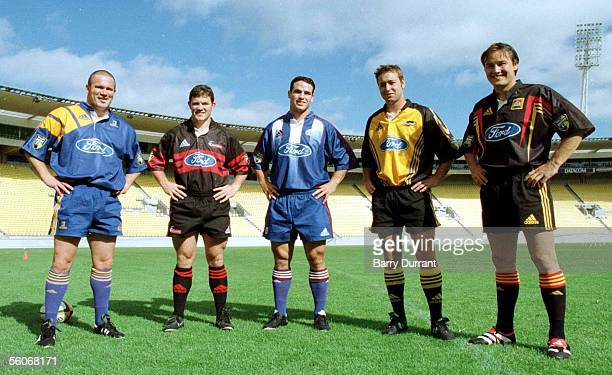 The new Super 12 rugby jerseys for the 2000 season modelled by their teams halbacks Highlanders Brett McCormack left Crusaders Aaron Flynn Blues Mark...