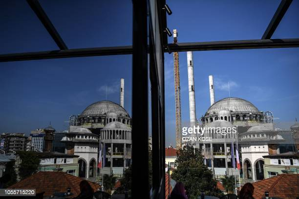 The New Taksim Mosque in construction is reflected in the window of the terrace of a cafe in Istanbul on October 31, 2018.