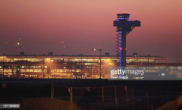 The new terminals and control tower of the new Berlin Brandenburg International Airport stand illuminated at sunrise on January 27 2012 in Berlin...