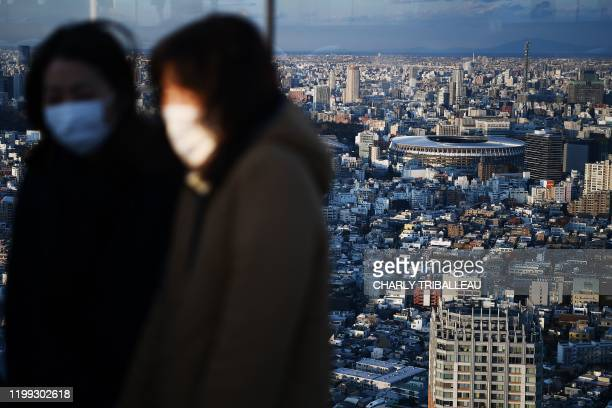 The New Tokyo Stadium the main venue for the 2020 Tokyo Olympic Games is seen past people wearing face masks at a rooftop viewing area in Tokyo on...