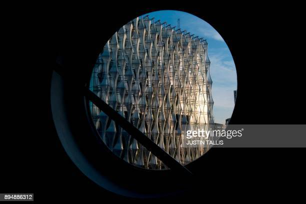 The new US Embassy is pictured through a round window of a near by residential building in Embassy Gardens in southwest London on December 18 2017...