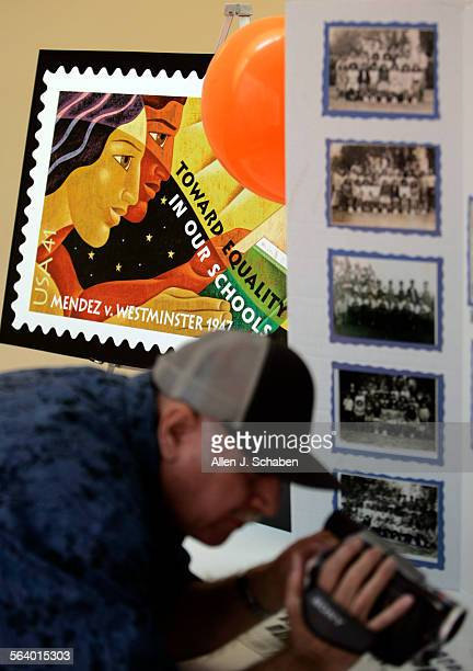 The new US Postal stamp Mendez v Westminster is unveiled while a person makes a recording of historical photos during Chapman University's 60th...