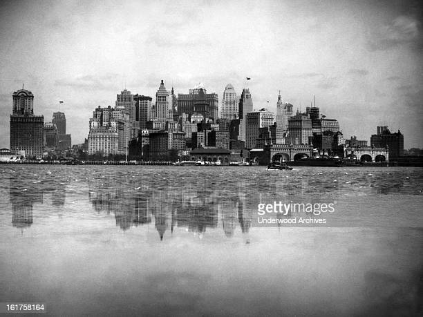 The New York Battery skyline reflected in the harbor waters New York New York mid 1920s