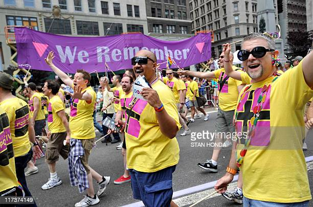 The New York City Gay Men's Chorus walks down Fifth Avenue past a sign commemorating AIDS victims during the New York City gay pride march June 26...