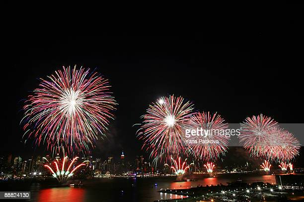 The New York City skyline is seen in the distance as fireworks explode over the Hudson River during the Macy's fireworks display July 4 2009 in...