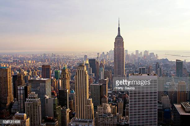 The New York City skyline seen from the observation deck at Rockefeller Center looking south at the Empire State Building and lower Manhattan
