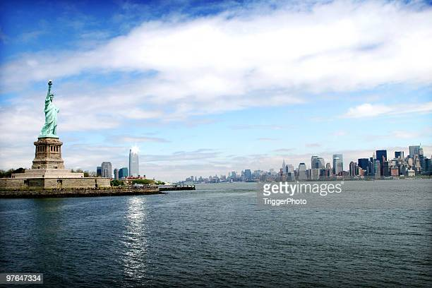 the new york city skyline with the statue of liberty - statue of liberty stock pictures, royalty-free photos & images