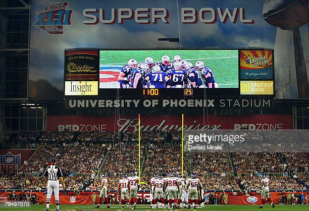 The New York Giants and the New England Patriots huddle up during the fourth quarter of Super Bowl XLII on February 3, 2008 at the University of...