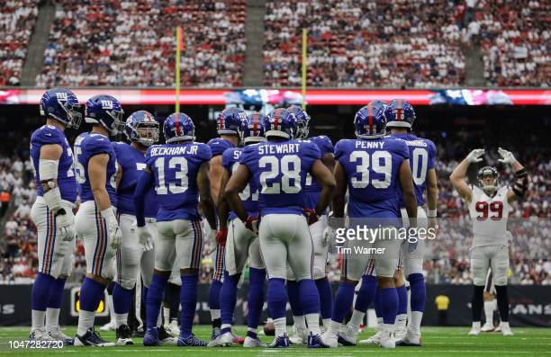 The New York Giants huddle as J.J. Watt of the Houston Texans signals for the crowd to make noise in the first half at NRG Stadium on September 23,...