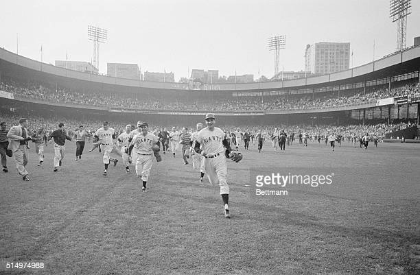 The New York Giants, led by a smiling Bobby Thomson charge toward their clubhouse ahead of eager fans after losing to the Pittsburgh Pirates with...