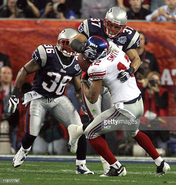 The New York Giants' Steve Smith is stopped by the New England Patriots' Rodney Harrison on a third and long play setting up a field goal in the...