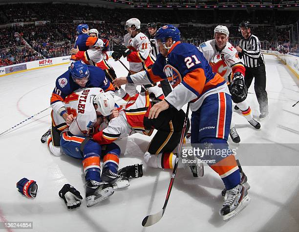 The New York Islanders and the Calgary Flames fight during the first period at the Nassau Veterans Memorial Coliseum on December 29 2011 in Uniondale...