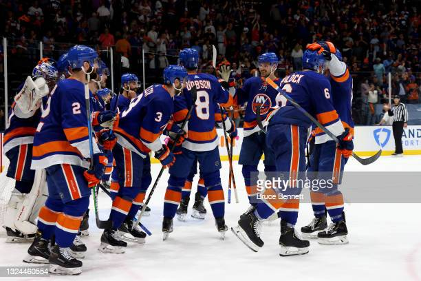 The New York Islanders celebrate after their 3-2 win against the Tampa Bay Lightning after Game Four of the Stanley Cup Semifinals during the 2021...