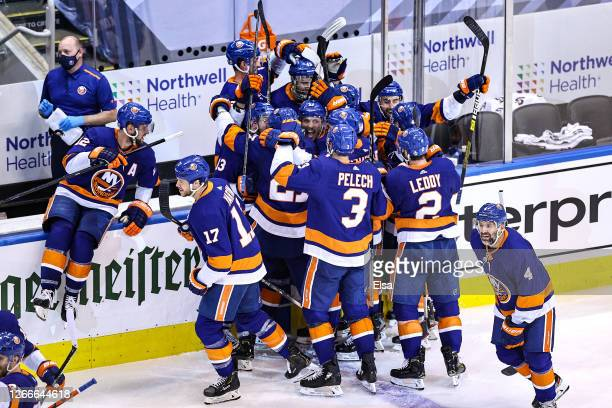The New York Islanders celebrate the game winning goal by Mathew Barzal against the Washington Capitals during the first overtime period for a 2-1...