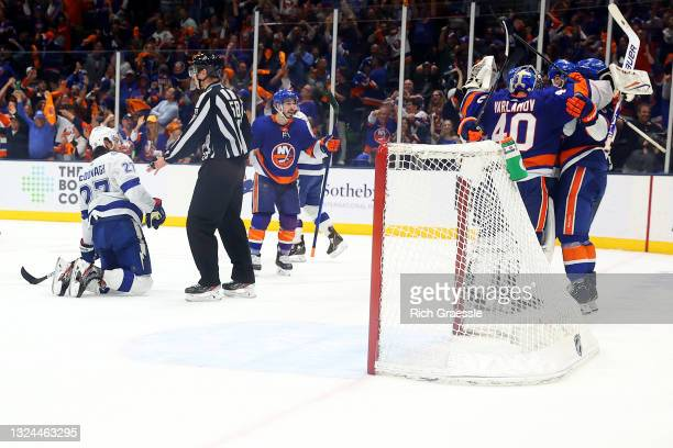 The New York Islanders celebrate their 3-2 win as Ryan McDonagh of the Tampa Bay Lightning reacts in Game Four of the Stanley Cup Semifinals during...