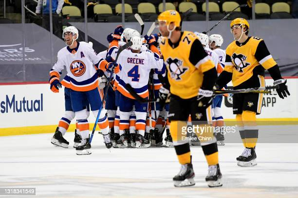 The New York Islanders celebrate their 4-3 win during overtime as Jeff Carter and John Marino of the Pittsburgh Penguins skate off the ice in Game...