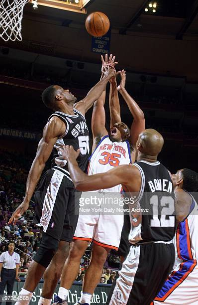 The New York Knicks' Clarence Weatherspoon shoots over the San Antonio Spurs' David Robinson at Madison Square Garden The Spurs' Bruce Bowen watches...