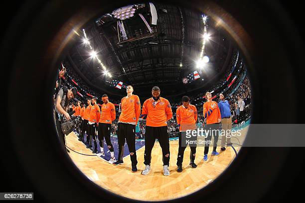 The New York Knicks stand on the court for the National Anthem before the game against the Charlotte Hornets on November 26 2016 at Spectrum Center...
