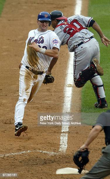 The New York Mets' Jason Phillips scores from third on a sacrifice fly as Atlanta Braves' catcher Henry Blanco misses the throw in the fourth at Shea...