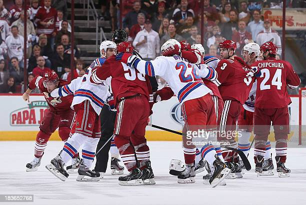 The New York Rangers and Phoenix Coyotes come together in a scrum during the home opening NHL game at Jobingcom Arena on October 3 2013 in Glendale...