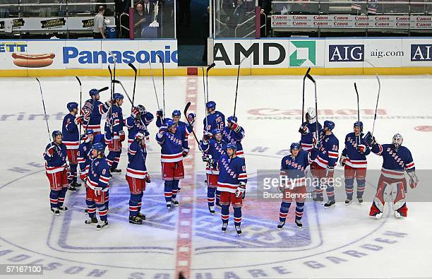 The New York Rangers stand at center ice and raise their sticks in the air to say thank you to the fans after the victory over the Boston Bruins on...