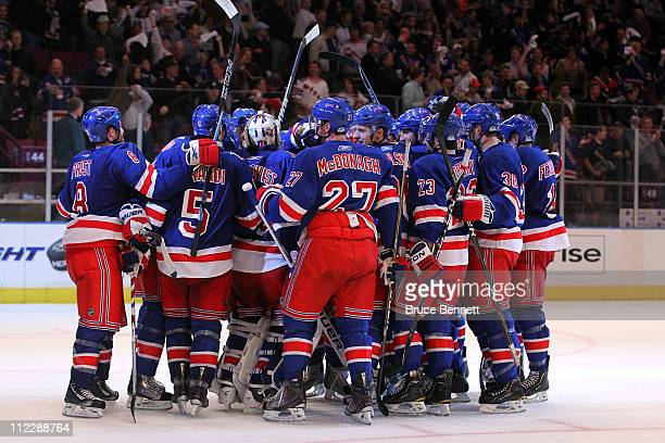 The New York Rangers surround goalie Henrik Lundqvist as they celebrate their 3-2 win against the Washington Capitals in Game Three of the Eastern...