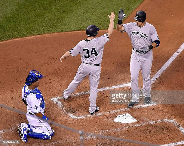 The New York Yankees' Aaron Judge right is congratulated by Brian McCann in front of Kansas City Royals catcher Salvador Perez after Judge hit a...