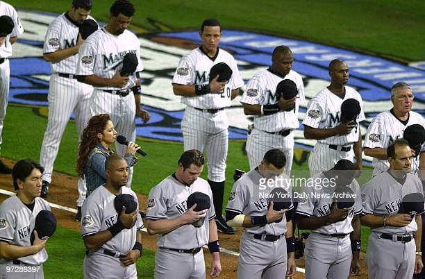 The New York Yankees and the Florida Marlins stand with heads bowed and their caps over their hearts as Gloria Estefan sings the National Anthem...