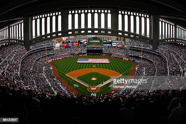 The New York Yankees and the Los Angeles Angels of Anaheim stand at attention during the National Anthem as a giant American flag is displayed on the...