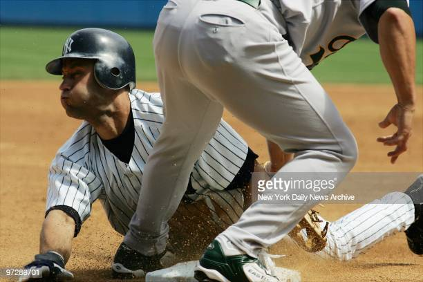 The New York Yankees' Derek Jeter is safe at third on a steal in a game against the Oakland A's at Yankee Stadium The Yanks won 51