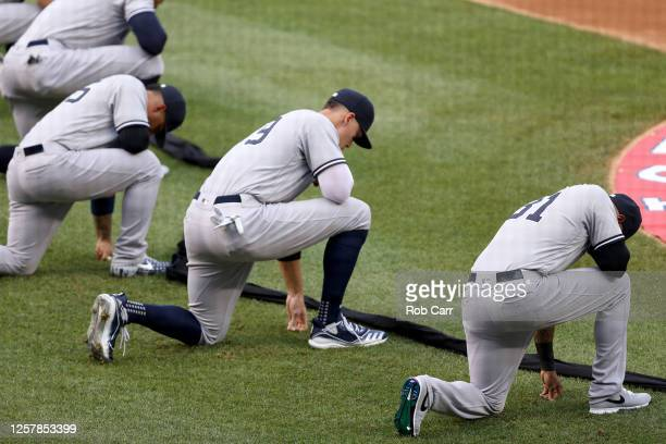 The New York Yankees kneel during a moment of silence prior to the game against the Washington Nationals at Nationals Park on July 23 2020 in...