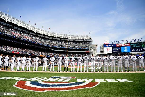 The New York Yankees stand for the National Anthem before the game against the Baltimore Orioles on Opening Day at Yankee Stadium on March 28 2019 in...