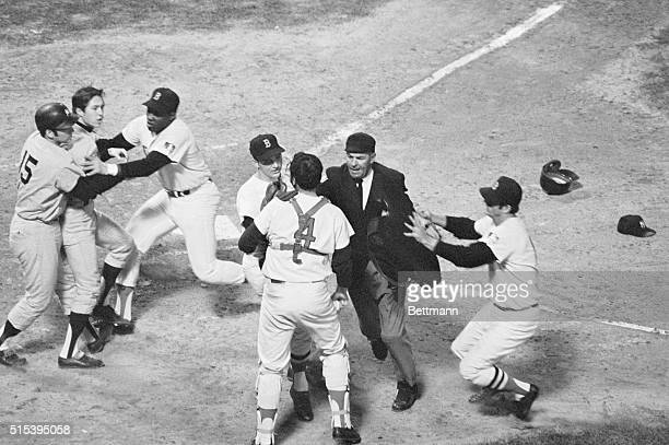 The New York Yankees' Thurman Munson and the Boston Red Sock's George Scott hold back Yanks' Bobby Murcer as Red Sox pitcher Ken Brett plate umpire...