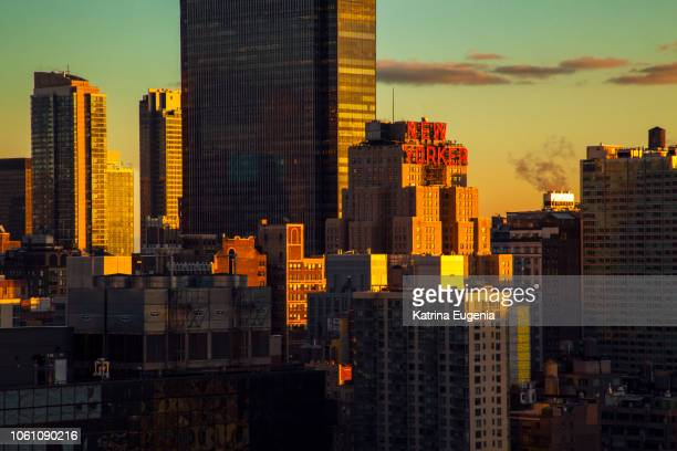 the new yorker hotel at sunset, new york city sunset, new yorker building - new yorker building stock photos and pictures