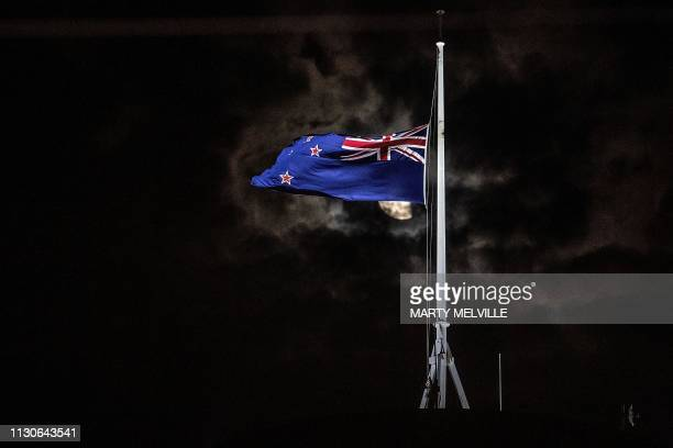 TOPSHOT The New Zealand national flag is flown at halfmast on a Parliament building in Wellington on March 15 after a shooting incident in...