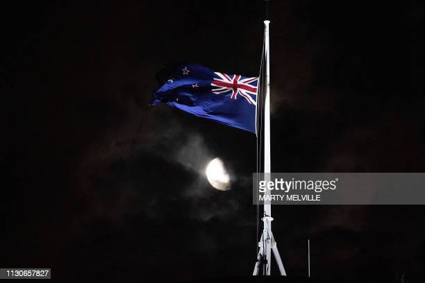 The New Zealand national flag is flown at halfmast on a Parliament building in Wellington on March 15 after a shooting incident in Christchurch...