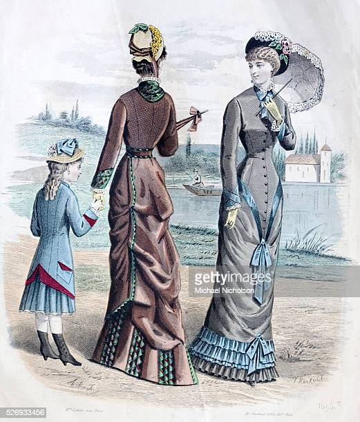The newest French fashions From a popular magazine of 1880 Two fashionably dressed women with parasols with a welldressed girl In the background is a...